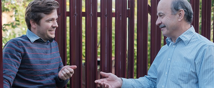 two neighbours talking next to fence