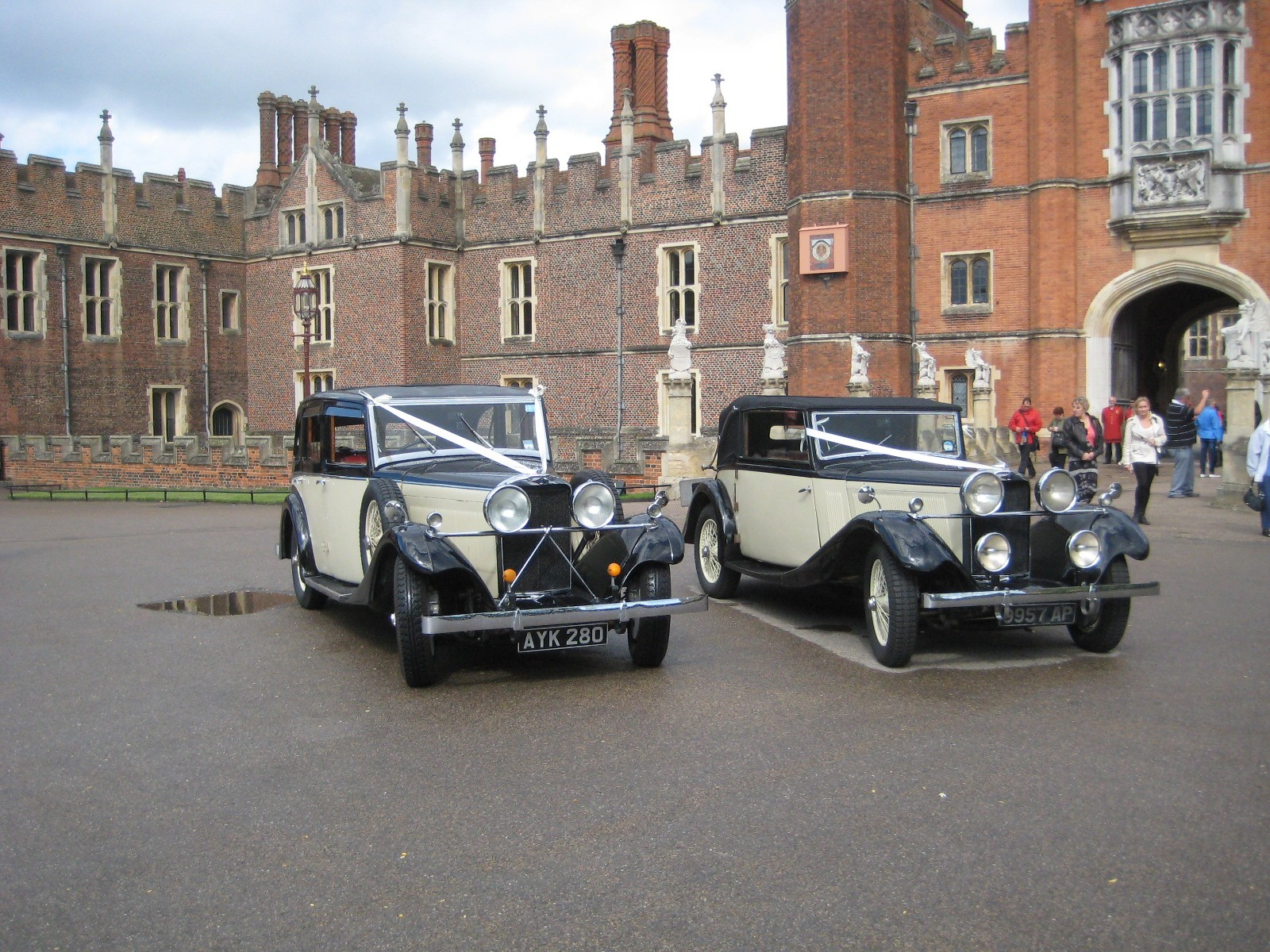 two vintage wedding cars in front of hampton court palace