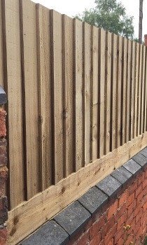 wooden fence on top of wall