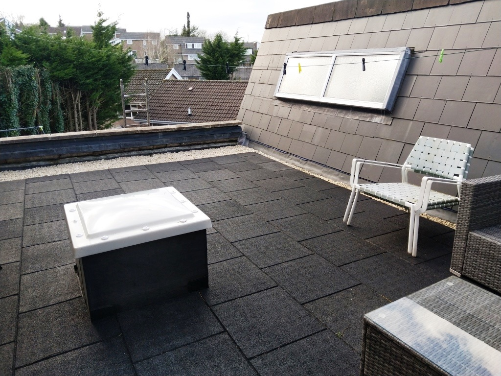 Flat roofing in Cardiff with black rubber tiles.