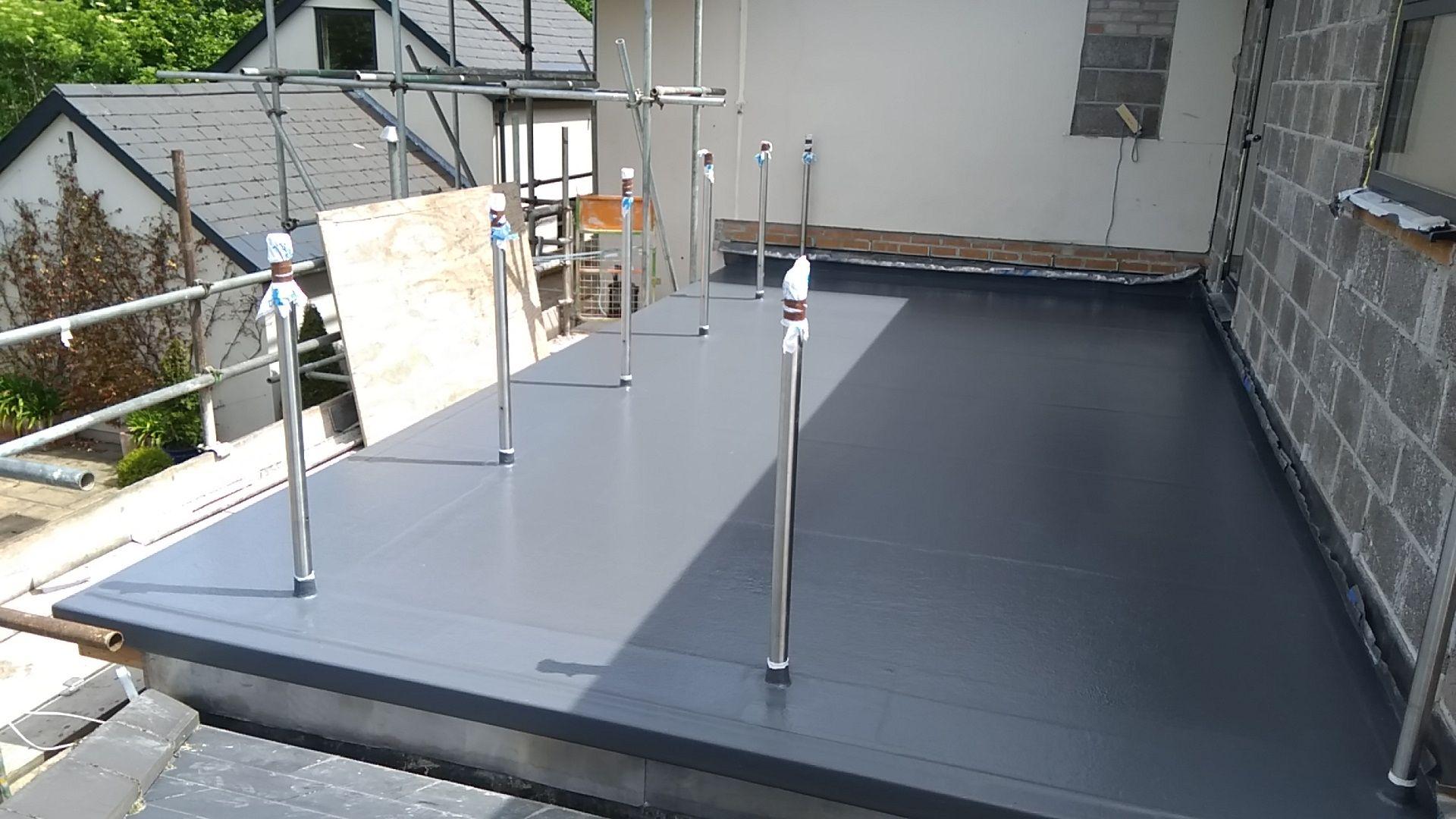Grey fibreglass flat roof with handrail posts.