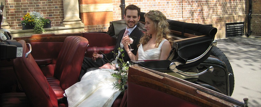 newlyweds sitting in open top roesch talbot