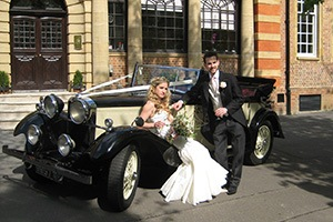 couple posing in vintage wedding cars