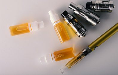 bottles of e-liquids and an electronic cigarette