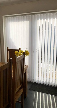 cream vertical blinds in a dining room