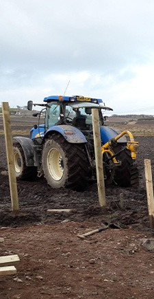 view of tractor building a fence