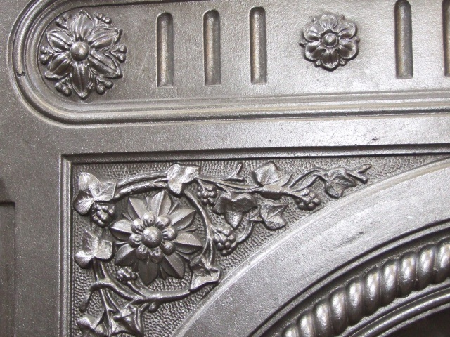 close up detail of cast iron antique fireplace surround