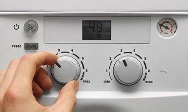 adjusting dials on a boiler
