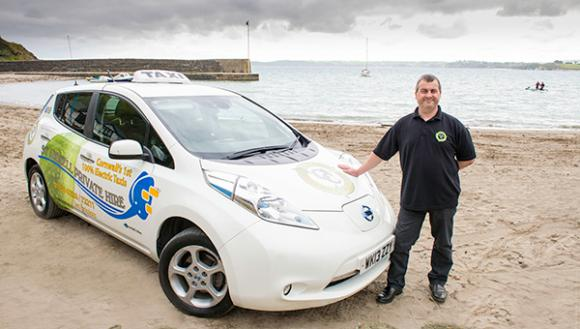 man standing next to a nissan leaf taxi on the beach