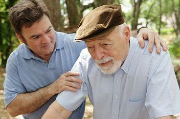 Companion providing support for elderly man